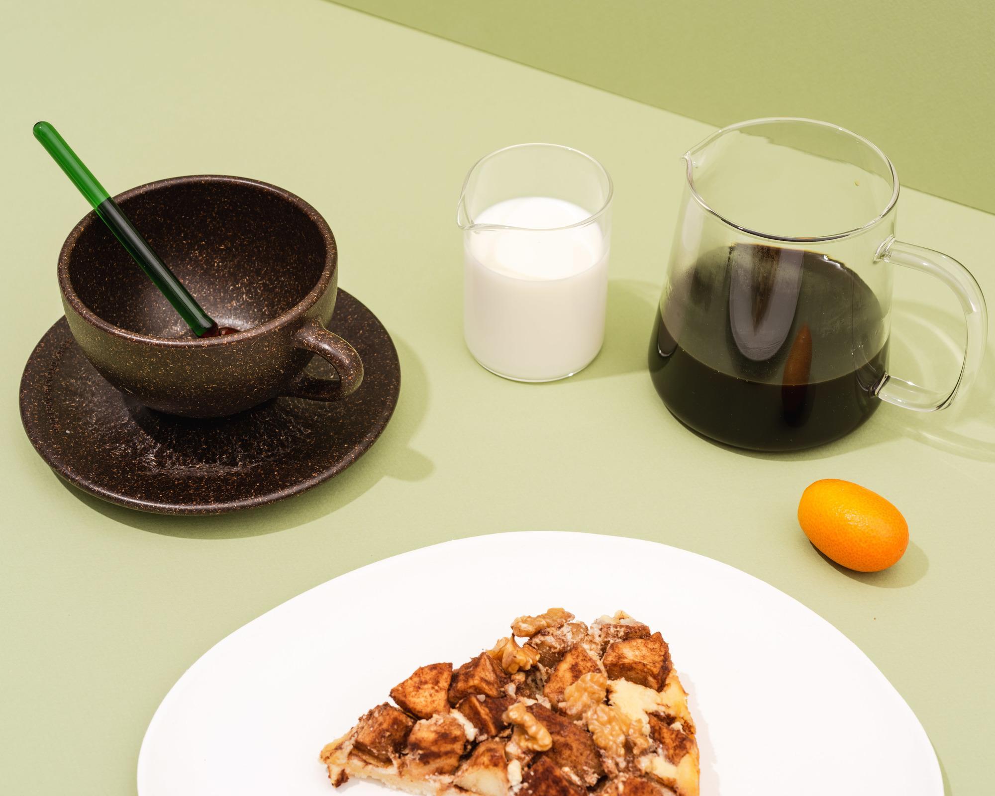 Kaffeeform Latte cup aus Kaffeesatz mit Unteratasse mit Filterkaffe, Milch und Gebäck auf grünem Hintergrund