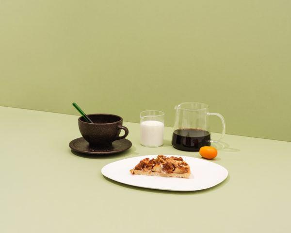 Kaffeeform Latte cup aus Kaffeesatz mit Untertasse Bild mit Filterkaffee, Milch und Gebäck auf grünem Hintergrund