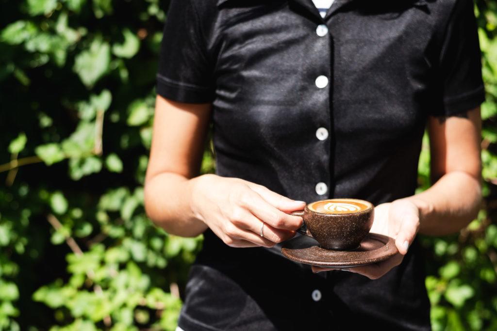 Person mit schwarzer Bluse hält Kaffeeform Cappuccino Cup mit Untertasse