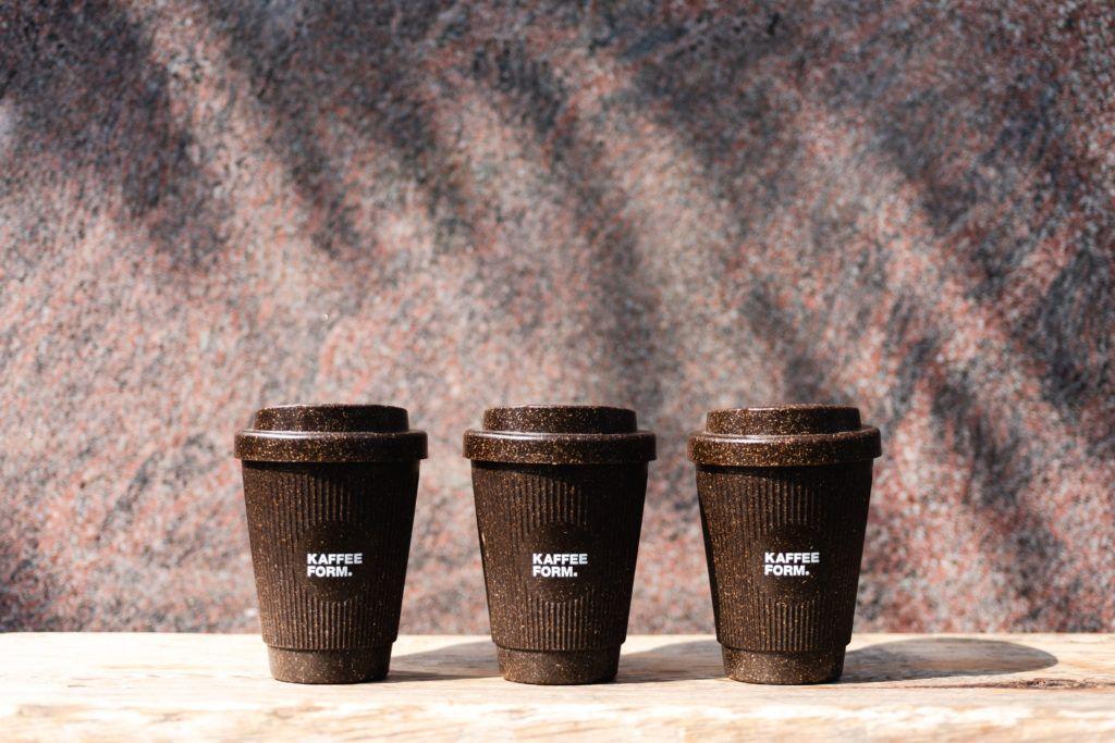 drei Weducer Cups mit Deckel und Kaffeeform Logo vor einer Steinwand