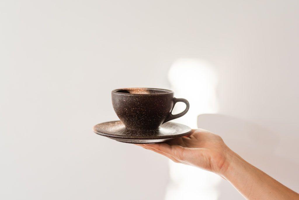 Hand hält Kaffeeform Espresso Cup vor einem weißem Hintergrund