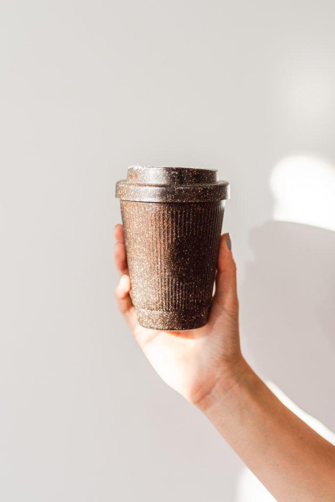 Hand hält Kaffeeform Weducer Cup vor einem weißem Hintergrund