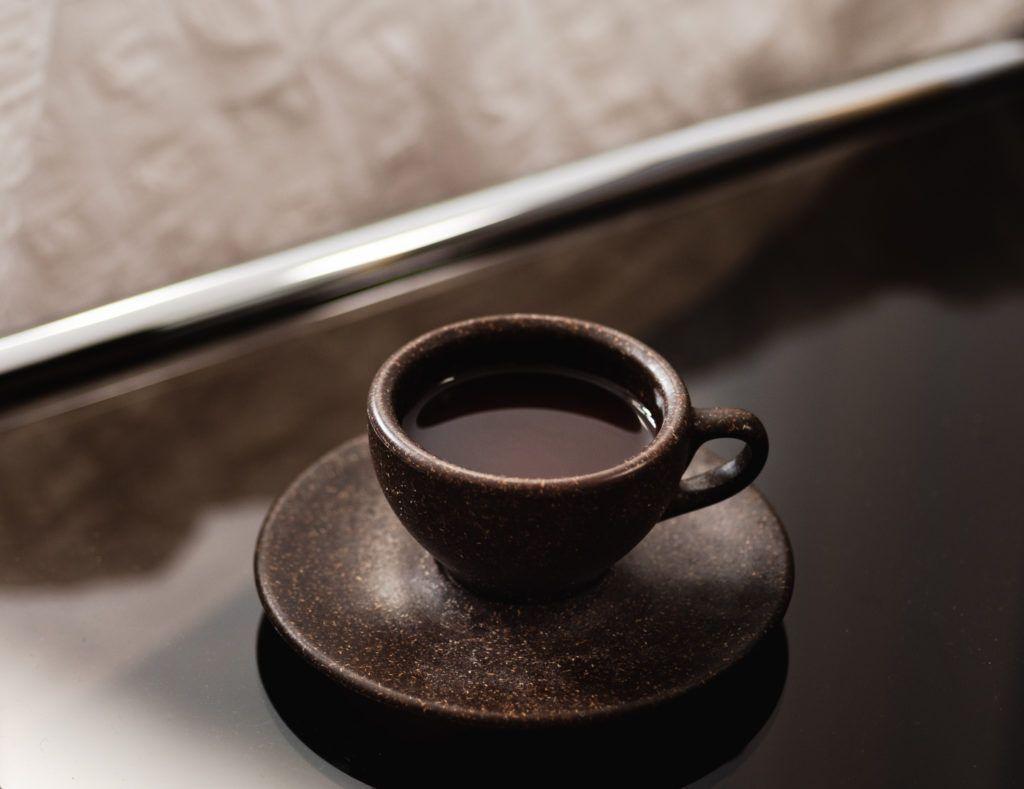 Kaffeeform Espresso cup mit Untertasse auf einem dunklem Tisch
