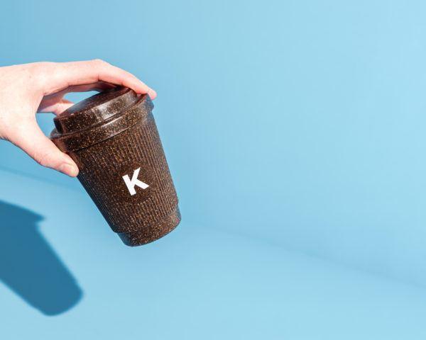 Hand hält Kaffeeform Alphabet Weducer Cup mit dem Buchstaben K vor einem blauen Hintergrund