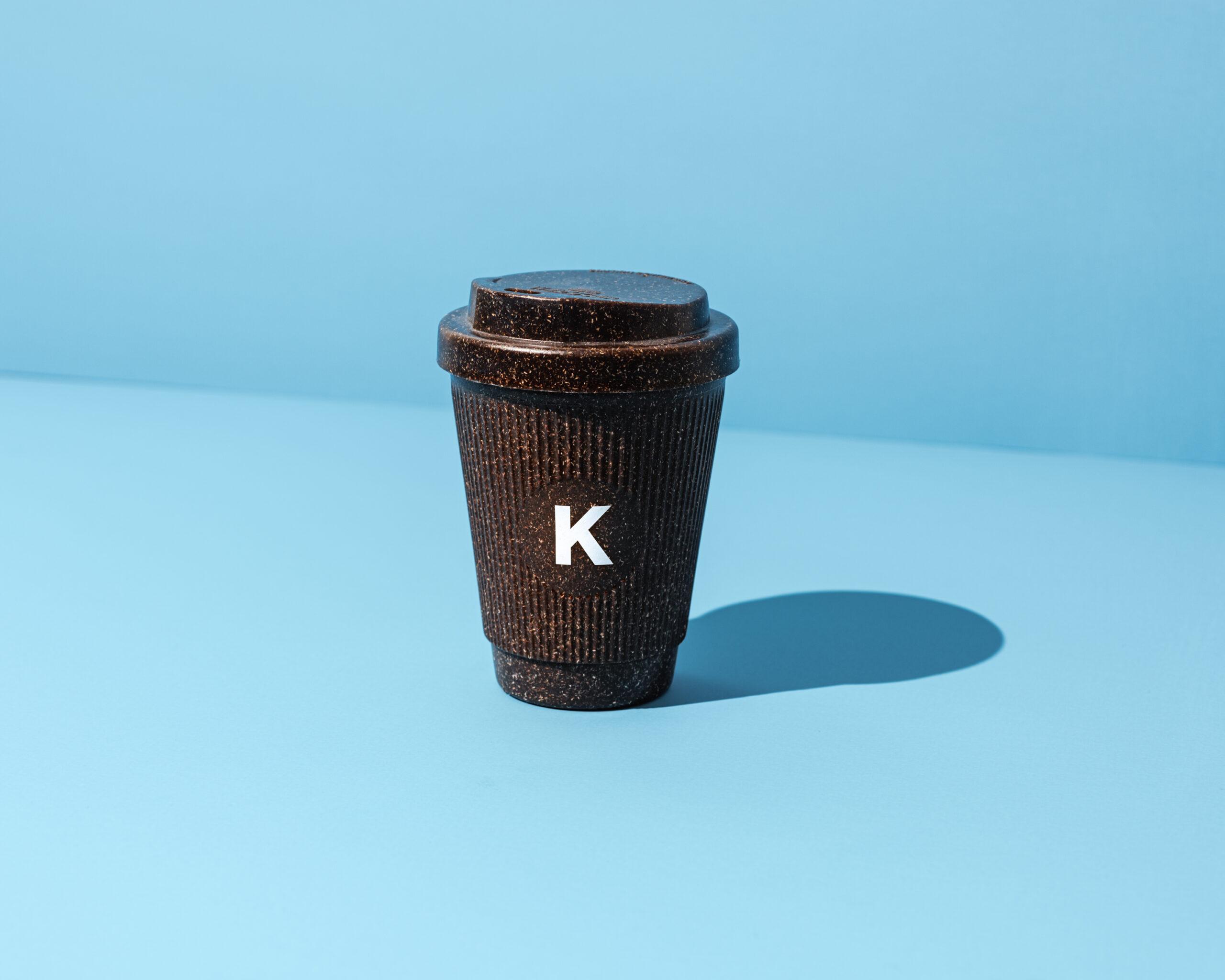 Kaffeeform Alphabet Weducer Cup mit dem Buchstaben K vor einem blauen Hintergrund