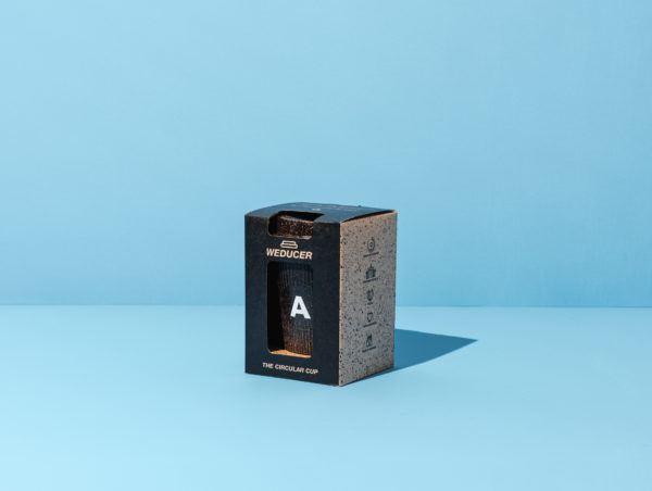 Kaffeeform Alphabet Weducer Cup mit dem Buchstaben A in der Verpackung vor einem blauen Hintergrund