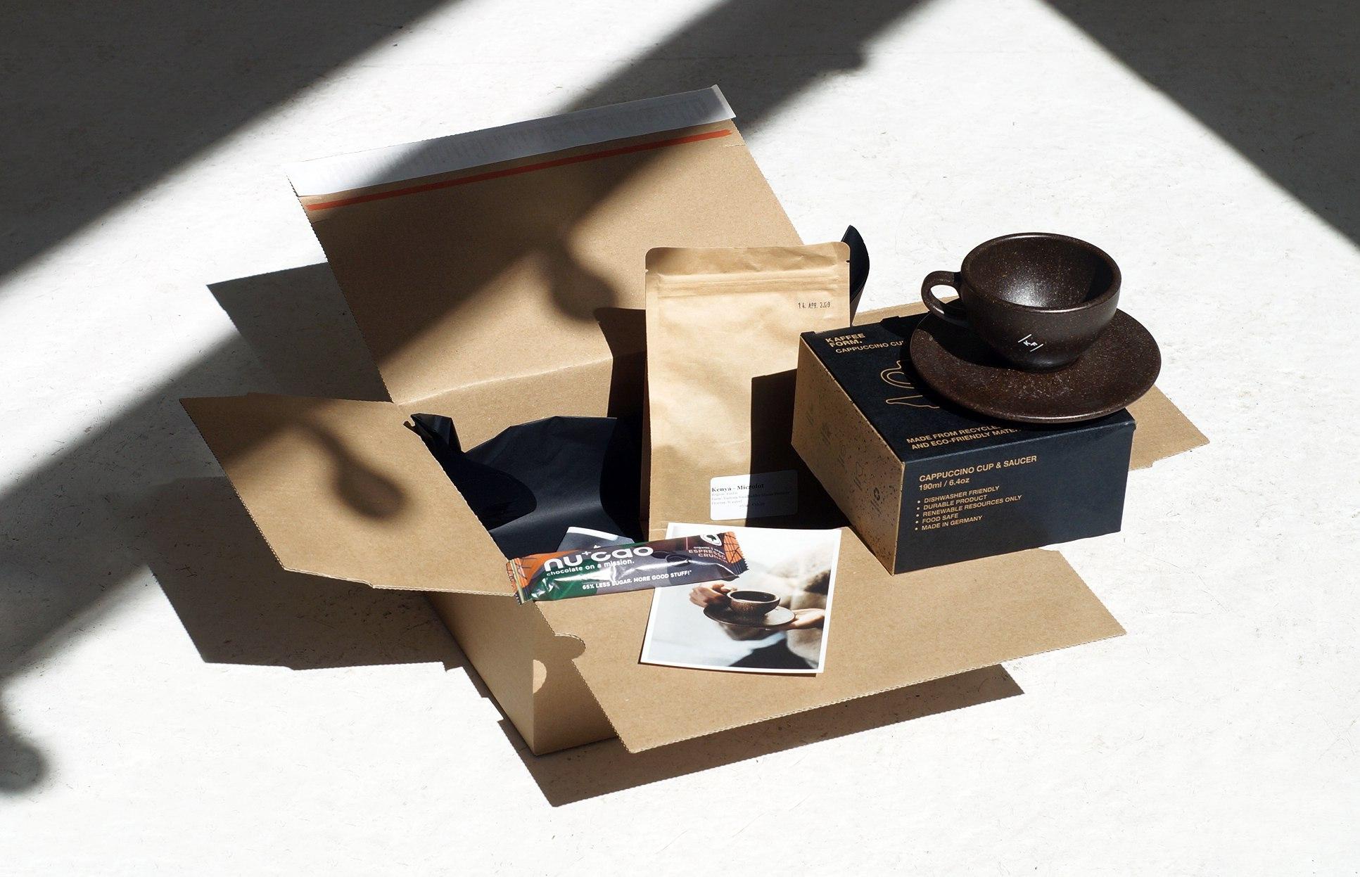 Kaffeeform Treat Box mit einer Tasse aus Kaffesatz, Kaffeebohnen, ein Nucao Riegel und einer Grußkarte