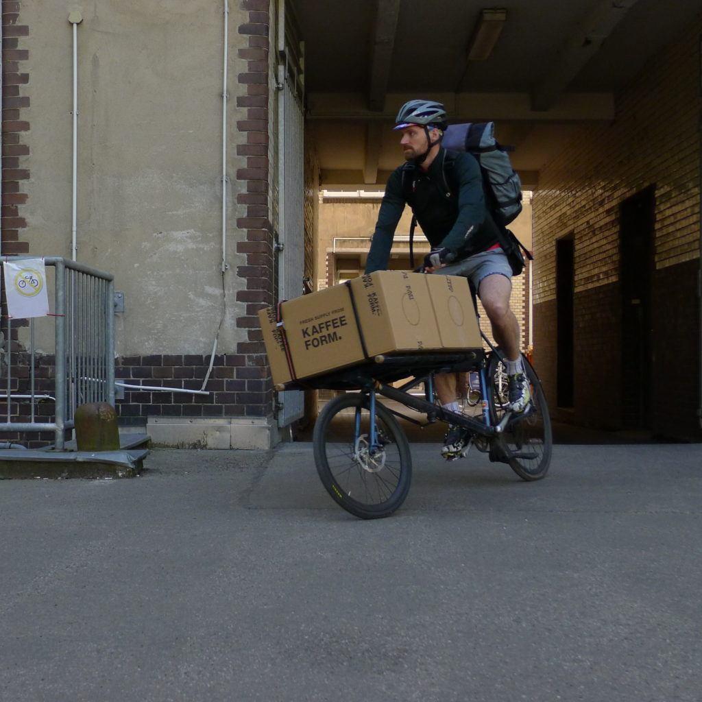 Fahrradkurier mit Kaffeeform Paket