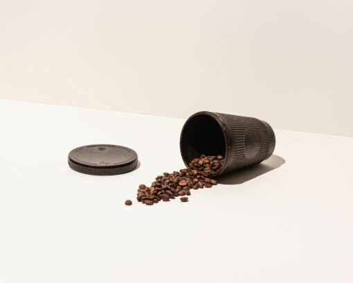Kaffeeform Weducer Cap neben dem Wedcuer Cup mit Kaffeebohnen gefüllt