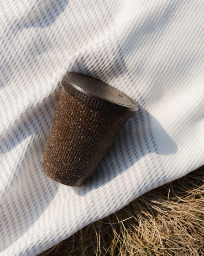 Weducer Cup mit dem Weducer Cap aufgeschraubt auf einer Picknick Decke