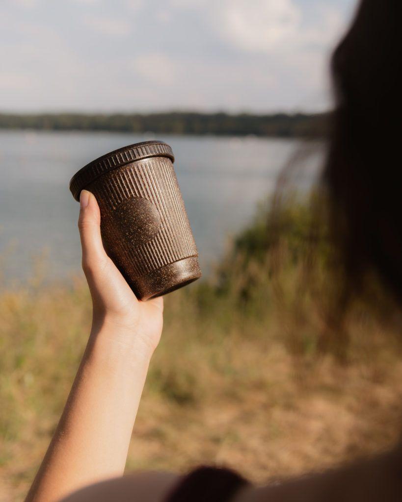 Weducer Cup mit dem Weducer Cap aufgeschraubt vor einem Naturhintergrund