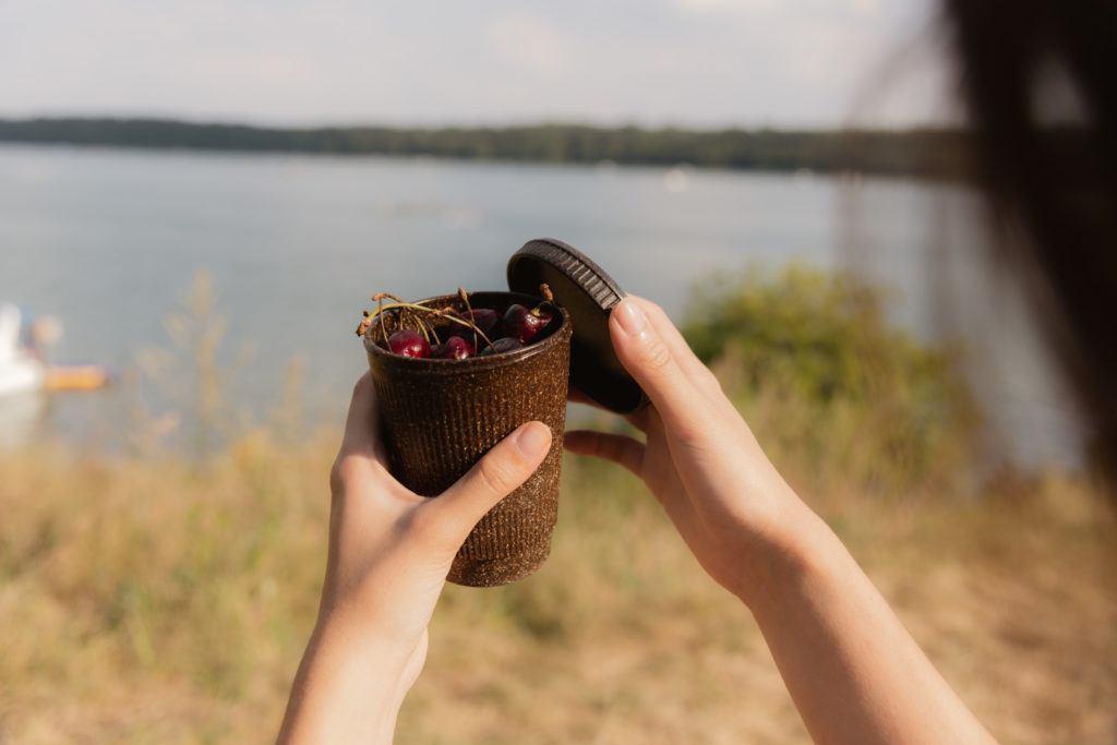 Person hält einen Weducer Cup gefüllt mit Kirschen in der Natur