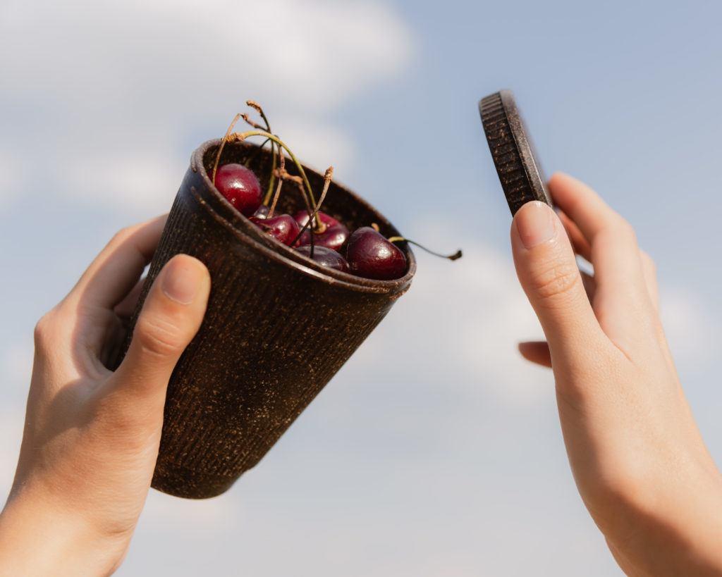 Person hält Weducer Cap und Cup gefüllt mit Kirschen