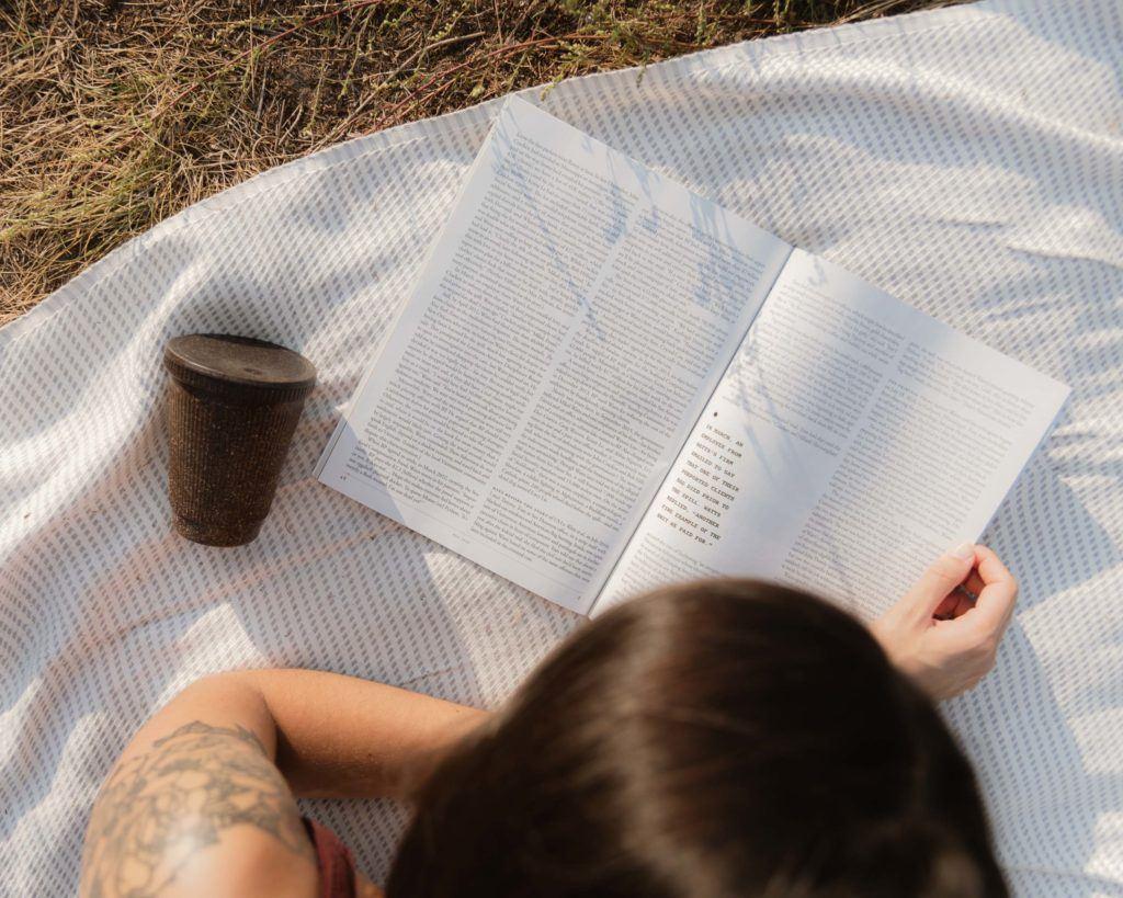 Person liest ein Magazin neben dem Weducer mit Cap auf einer Picknickdecke