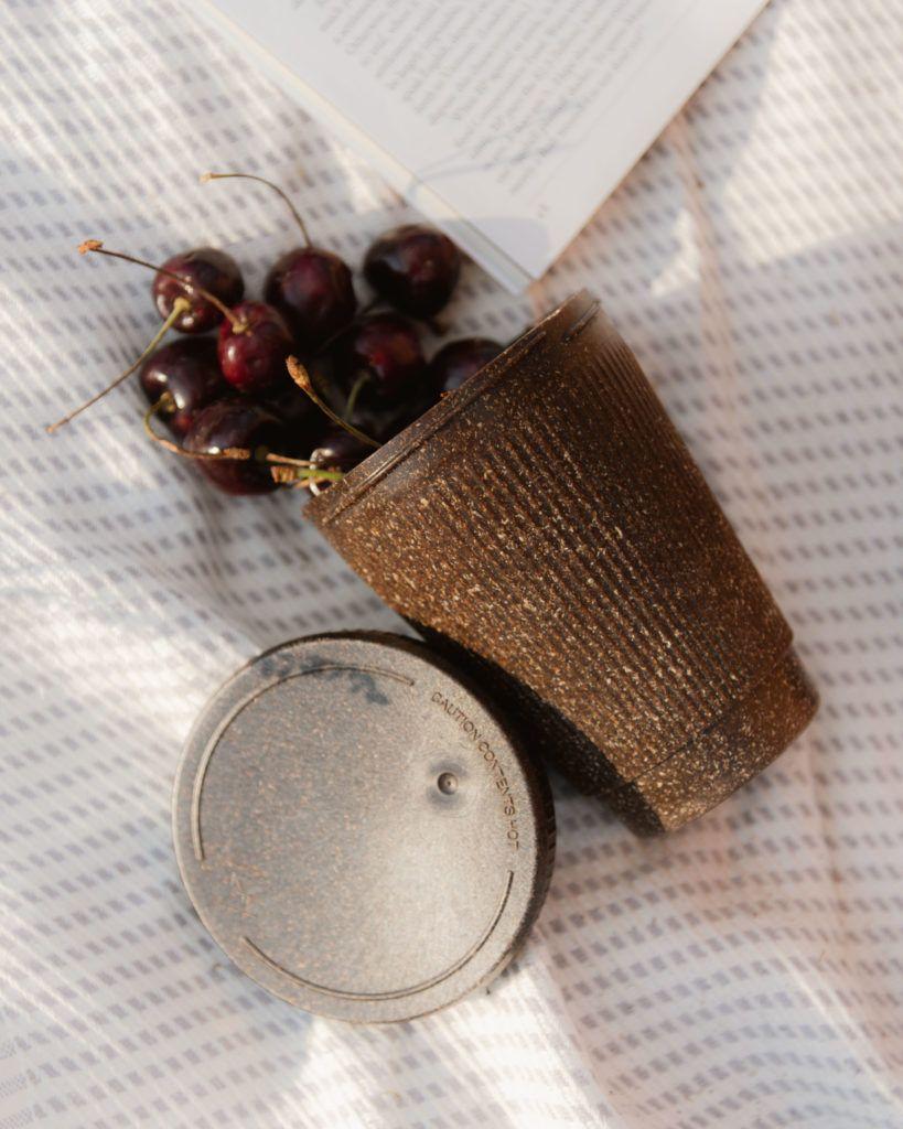 Weducer Cap neben dem Weducer Cup gefüllt mit Kirschen auf einer Picknickdecke