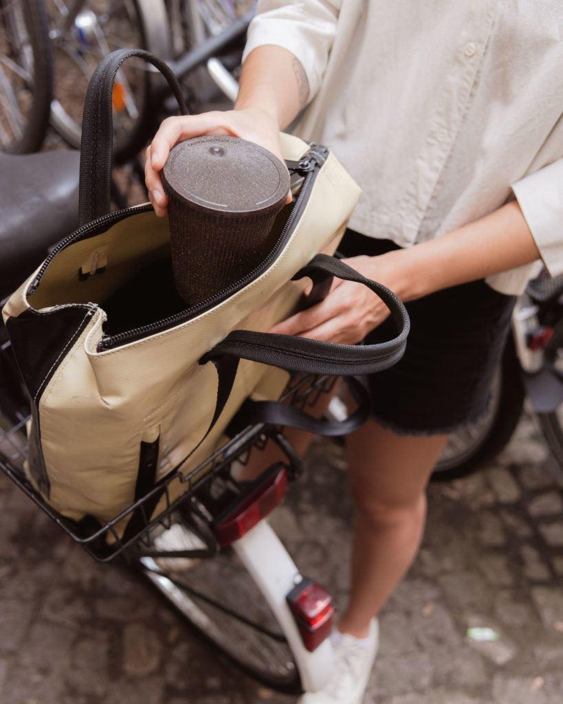 Person packt den Kaffeeform Weducer Cup mit Weducer Cap in eine Fahrradtasche