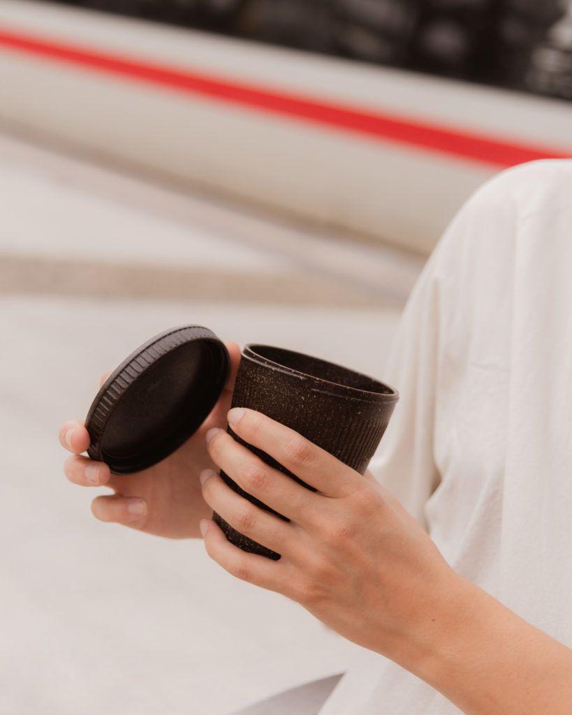 Person hält den Kaffeeform Weducer Cup mit dem Weducer Cap vor einem neutralen Hintergrund