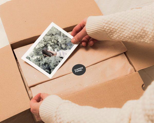 Person packt ein Paket für den Kaffeeform Geschenkservice