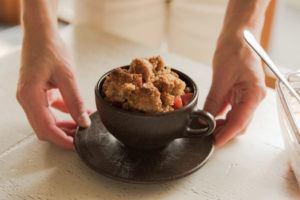 Hand hält einen Kaffeeform Cup gefüllt mit Apfel Crumble