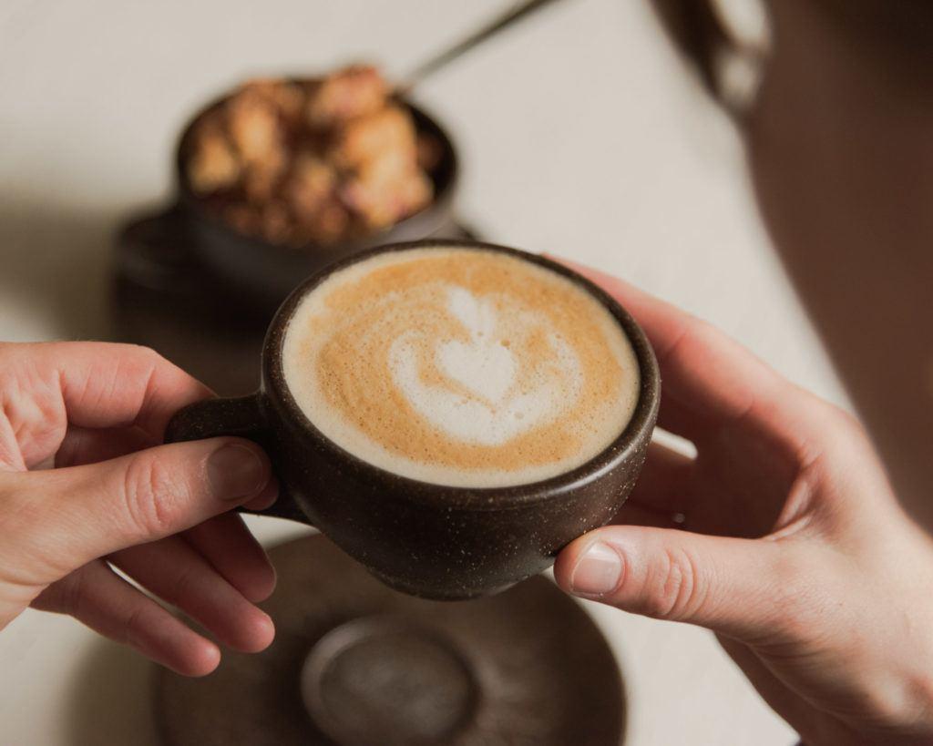 Person trink einen Cappuccino aus einem Kaffeeform Cup