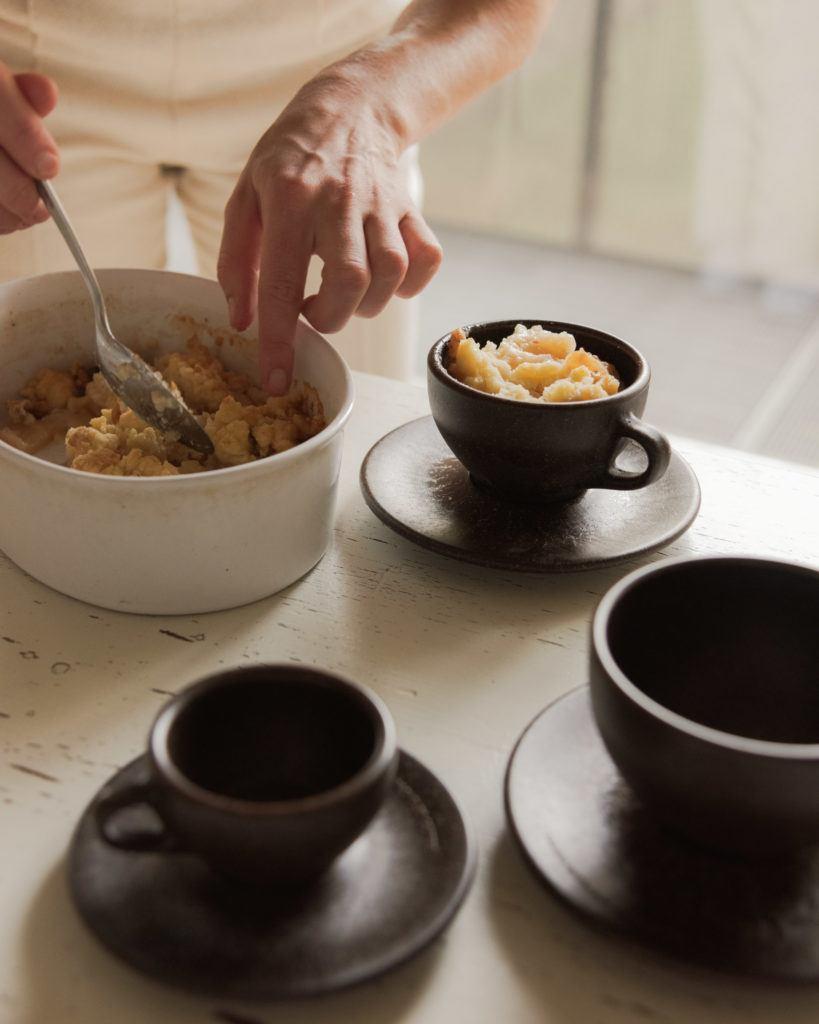 Person bereitet Crumble zu an einem Tisch mit Kaffeeform Cups